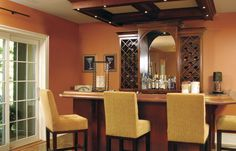 A new, convenient wet bar with a granite top and wood tones fits cozily in this living space enclosed by peach-colored walls and stained-birch coffering overhead.