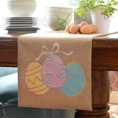 Decorate with ease this Easter season with our Easter Egg Burlap Table Runner! Its gingham embroidered Easter eggs on burlap have all the elements of country style and a perfect addition for your Easter decor!