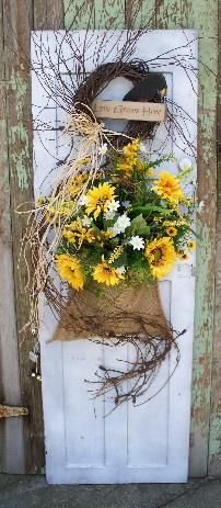 Old small door with burlap bag...sunflowers...grapevine...lights..small wreath and crow  $50
