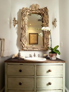 Rustic powder room design with brach mirror, repurposed wood cabinet single bathroom vanity and orchid.