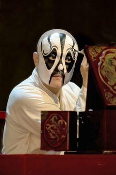 Performer applying make-up at Peking Opera