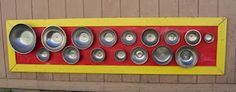 A Banging Board - metal bowls and pans mounted on a board - on a Montessori toddler's playground