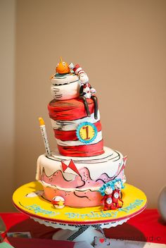 """For my little girls 1st birthday I decided on the theme of """"Cat in the Hat"""" since she loves the show as little as she is. For the cake I wanted to keep it simple and incorporate all the traditional 'Cat in the Hat' characters from the story book. Layers of red velvet and vanilla cake was a fun way of incorporating the """"hat"""" and having guests enjoy both flavours."""