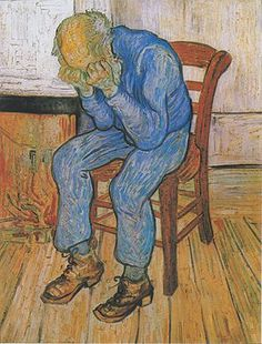 An old man with a bald head is sitting on a yellow chair by his fire. There is a low fire in the grate. He is dressed in blue clothes. He is holding his head in his hands.