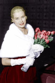Grace Kelly in a red dress and a fur stole at a Cannes Film Festival premiere, May 1955