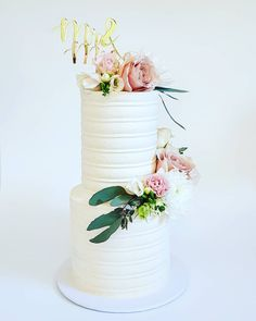 Wedding Cake: 2 tier, textured buttercream, with fresh blooms.