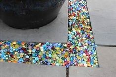 Colored glass Instead of gravel in the garden or patio...you can get these at the dollar store.