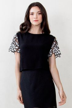 Flora  34.00 Black knit top with a floral crochet trim on the sleeves. Split detail on back with a zipper closure. 100% Polyester. Care: Hand wash Only