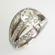 Old-cut diamond centre-stone, flanked by small, brilliant round-cut diamonds, set in platinum