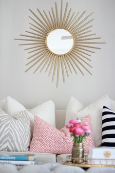 Chic living room featuring Martha Stewart Living Wales Metal Antique Gold Framed Mirror over high-back sofa filled with collection of pillows: white and gray zebra pillow, Cailtin Wilson Textiles Coral Fretwork Pillow and black and white striped pillow.