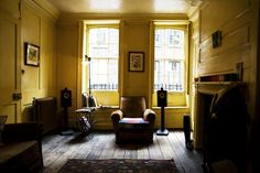 A wood panelled room, with polished wood floor, partly covered by a rug in the foreground. An armchair is between two sash windows,…
