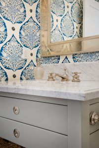 Bathroom Ideas. Bathroom Ideas. Beautiful blue and gray powder room features a gray single washstand fitted with polished nickel hardware and a Carrera marble countertop finished with an oval sink and a polished nickel faucet kit positioned beneath a champagne gold beveled mirror fixed on a wall covered in Galbraith & Paul Lotus Wallpaper. bathroom-ideas #BathroomIdeas