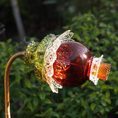 THIS FLOWER: This flower is made with a moss green hobnail candy dish, a clear patterned dish, bowl, a ruby red vase, a patterned clear glass dish, and an amber brown 1,000 eyes votive. It measures approx. 11 from end to end, and is approx. 8 at its widest point, patterned clear
