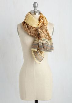 Plans to travel the world? Take this rectangular scarf as your go-to accessory, and watch as it adds beautiful brilliance to your already-epic photos. This sand-colored wrap is bursting with a rust, brown, blue, and peach mix of designs that look and feel fab on every continent!
