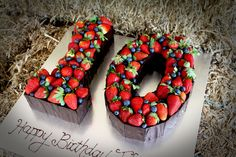 Chocolate mud number 10 cake decorated with fresh berries and chocolate shards.