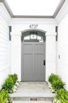 A beautiful white brick home features a gorgeous gray shiplap side door fixed under an arched doorway.