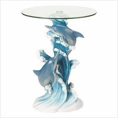 "Dolphins Accent Table Enhance your decor with a statuary table of incomparable artistry! Lovingly sculpted column base perfectly captures a dolphin pair's light-hearted joy and exuberant grace as they play amongst the foaming waves.  Flowing lines and intricate details combine to create a stunning work of functional art! Polystone base; glass top. May require additional freight charge. 19"" diameter x 24 1/8"" high. UPC: 849179005047. http://www.cantersbestdeals.com"