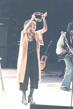 Stevie onstage ~ ☆♥❤♥☆ ~ tambourine held high above her head, and wearing…