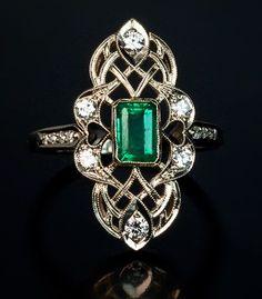 A Vintage Art Deco Emerald and Diamond Ring, Circa 1930. A 14K white gold openwork milgrain ring is set with an emerald-cut emerald, six brilliant diamonds and eight single-cut diamonds.