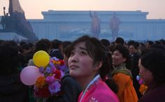 A North Korean woman looks up at balloons overhead at the end of an unveiling ceremony for statues of the late leaders Kim Il Sung and Kim Jong Il in Pyongyang, on April 13, 2012.