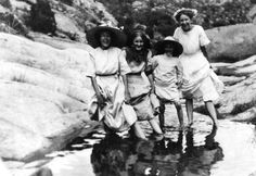 Four young ladies dipping their feet in a pool of water around 1911 near Bisbee, Arizona.  This image is from the photograph collection of the Bisbee Mining  Historical Museum.