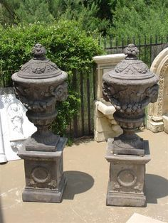Pair of Rams Head Urns on Bases in Aged Stone Finish