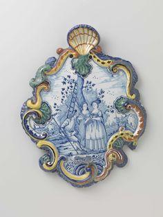 Anonymous | plaat in cartouchevorm met in blauw een landschap met drie figuren onder een boom, binnen een veelkleurige bloemenrand, Anonymous, c. 1750 - c. 1780 | plaat van faïence, cartouchevormig. Beschilderd in blauw met drie figuren onder een boom, binnen een veelkleurige rand.