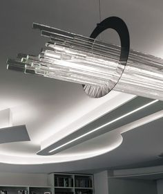 Olimpic lamp composed by glass slats 8 mm extra thick cut and grinded by hand arranged horizontally and resting on four polished stainless steel rings