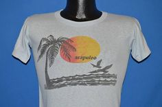 Chest 15.5 in.  Length 22.5 in.   Content: 100% Cotton  Tag Brand: Loris  This light blue vintage t-shirt is a souvenir from Acapulco on the Pacific ocean coast of Mexico. The graphic is a beach with a single palm tree and a sunset about to touch the horizon.  This shirt is an Adult Extra Small.         17-06-75563