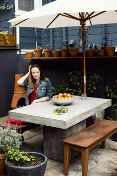 "clothing designer Courtney Klein at home in San Francisco's Mission District; her outdoor concrete dining table is the Fuze Grey Dining Table from CB2 ($999). Measuring 35.5""W by 57""L and 30""H, it seats six."