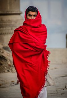 Cloaked+in+Red+-+A+striking+young+man,+cloaked+in+red,+walks+along+the+Ghats+which+line+the+Ganges+River+in+Varanasi,+India.+