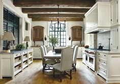 Exposed rustic beams, cabinetry that looks like furniture, those chairs, touches of black, very beautiful.