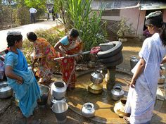 Women use a poorly maintained handpump in India.  Water.org water programs employ a community engagement component, which provides the training and resources necessary to maintain and repair their water source in the future.