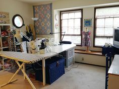 I like this set up where the sewing table and ironing board make an island in the room