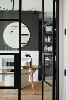 Opening into the office, steel-paneled glass doors are used throughout the house to maintain a sense of openness. Save for a finished basement and a few walls above ground, this Ontario, Canada residence, designed by Nicholas Ancerl of Ancerl Studio, was built completely anew to fulfill the homeowner's wishes of a country-chic home. #interiordesign #architecture #homedecor Ontario, Black Accent Walls, Black Walls, Black Window Frames, Toronto, Style Loft, Industrial Windows, White Oak Wood, Interiores Design