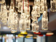 Classic Coke bottle pendent lamps hang over the coffee bar counter at the Cpca-Cola factory