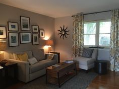 Sitting room for a client. Henry Sofa/Dove Gray-West Elm, Wall Color-Alpaca/Sherwin Williams, Chair and Curtains/Birch Lane, Parsons Side Tables/Pier 1, Rug/Pottery Barn, Lamps/Home Goods, Pillows and Throw/West Elm and Marshalls and featuring a gallery wall of owners photos.