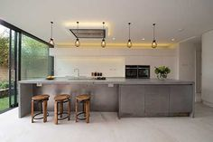4m-long concrete island worktop with end panels. Island seating and cupboards