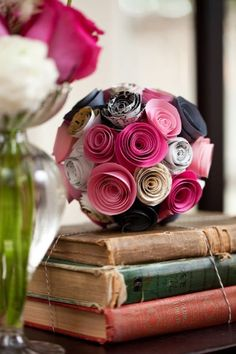 Handmade paper flower bouquet made from pink and grey card stock on top of vintage books wrapped in twine. Flowers - www.intrigue-desi... Photos - www.lizandryan.com Paper & Design - www.allisonbarnhi... Vintage Rentals @2hands studios studios @Allison j.d.m Barnhill @Liz Mester and Ryan Bower (I am missing a number of vendors. This will be updated shortly to list everyone's credit)