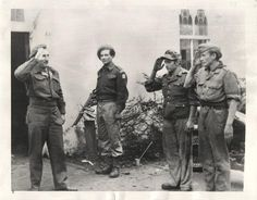 1945- German prisoners of war, guarded by soldier with tommy gun, snap to salute a Jewish officer at prison camp near Haarlem, Holland. Brigade of Jewish troops was in charge of the camp.