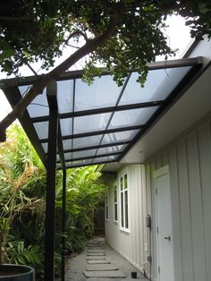 Small patio cover with bearing beam and polycarbonate (LEXAN) roof panels. It's a heat cut panel that will let light in but heat out. see  https://kunkelworks.com/patio-covers/
