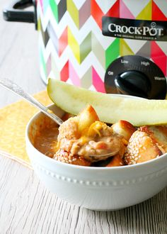 Perfect Slow Cooker Cheeseburger Soup, topped with homemade sesame bagel croutons, shredded cheddar cheese and served with a big pickle spear.
