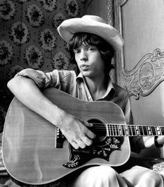 A very (very) young Mick Jagger in hat, playing his Gibson acoustic.