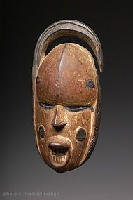 A fine Igbo 'okoroshi' mask - The masquerade of 'okoroshi' embodies both the dark side (masculine) and joyous, lighter side (feminine) of life. Certain grotesque and cluttered images represent evil and 'heavy' events, and whitened face masks, such as this fine, old example are images of benign, beautiful spirits and experiences. They are found less frequently than their aggressive counterparts, as if to say that life, on the whole, is quite tough most of the time. The dance which they are…