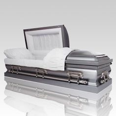 The Stainless Semi-Precious Metal Caskets are crafted from premium stainless steel and features a stately, brushed natural finish with subtle hued highlights. This gasketed casket follows the half-couch design and features the Eterna Rest adjustable bedding system. The exterior is decorated with white velvet interior and includes a matching pillow and throw.