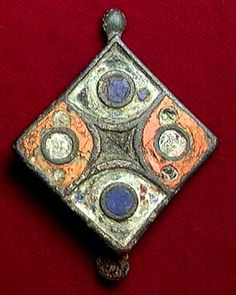 ROMANO-BRITISH ENAMELED BROOCH, ca. 4th-5th century. Of rhomboidal form with inlays of white, blue and orange enamel remaining. Pin lost. 1.5 inches. Beautiful bright colors!