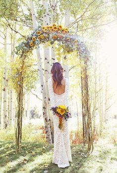 This wedding arch is glorious. The burst of sunflowers at the top remind one of the sun rising while the soft purple (lavender?) softens the look which is twined around a woodland arch.