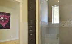 Built in storage cupboard into wall adjacent to shower. You would need to match cupboard with vanity doors.