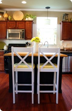 a kitchen with dark cabinets and wood...with some white splashed in