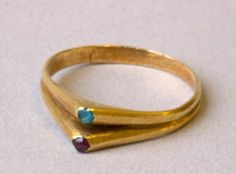 Finger-ring; gold; ruby, turquoise. The stirrup-shaped hoop divides into a double ring with two bezels, each with a different gemstone.